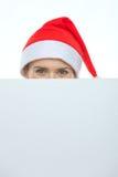 Femelle dans le chapeau de Noël se cachant derrière le panneau-réclame Photos libres de droits