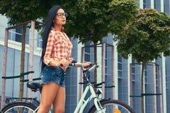 Femelle de brune de beauté portant des caleçons d'une chemise rose et de denim de flanelle en verres, se tenant avec le vélo de v Image libre de droits