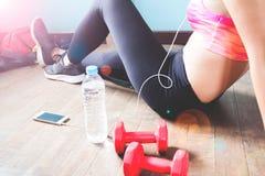 Femelle de forme physique dans le pantalon noir et des espadrilles détendant après séance d'entraînement avec de l'eau les haltèr Image stock