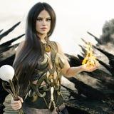 Femelle de magicien d'imagination avec des flammes venant de ses mains et d'une île mythique de crâne à l'arrière-plan illustration de vecteur