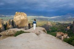 Femelle de photographe avec l'appareil-photo dans le plaid blanc au bord du regard de roche sur les monastères de Meteora Meteora Photos libres de droits