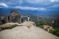 Femelle de photographe avec l'appareil-photo dans le plaid blanc au bord du regard de roche sur les monastères de Meteora Meteora Photographie stock libre de droits