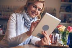 Femelle de sourire à l'aide du comprimé numérique Images stock