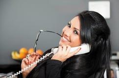 Femelle de sourire au téléphone image stock