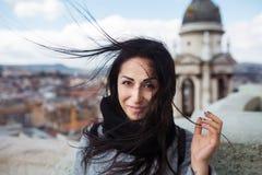 Femelle de sourire avec de longs cheveux noirs soufflant par le vent Image libre de droits