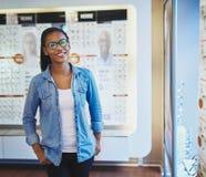 Femelle de sourire devant l'affichage de lunettes Photographie stock