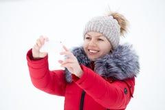 Femelle de sourire heureuse dans la veste rouge d'hiver prenant la photo avec le SM Photographie stock
