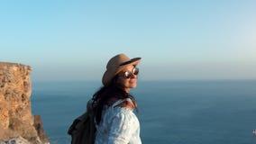 Femelle de voyage de hippie ayant la marche de sourire d'amusement sur la montagne au-dessus de la mer au coucher du soleil banque de vidéos