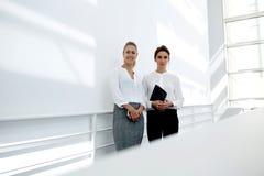 Femelle deux de charme dans le tenue de soirée posant pour l'appareil-photo sur le fond blanc de mur avec le secteur d'espace de  Photographie stock libre de droits