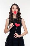 Femelle drôle employant de faux lèvres et appui verticaux de coeur sur des bâtons Photo stock