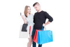 Femelle et ami gais employant la carte de crédit Photographie stock
