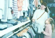 Femelle et choisissant vêtx pour le bébé du magasin de children's Images libres de droits