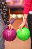 Femelle et mâle remet des billes de fixation dans le bowling c Image libre de droits