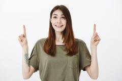 Femelle européenne élégante mignonne avec le tatouage en main souriant largement avec l'excitation, se dirigeant et recherchant,  photos stock