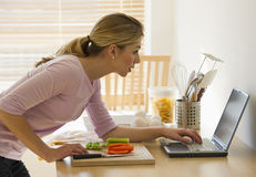 Femelle faisant cuire et regardant l'ordinateur portatif dans la cuisine Photographie stock