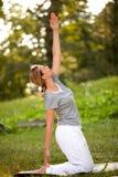 Femelle faisant des exercices physiques en parc vert Photo stock