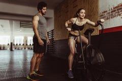 Femelle faisant la cardio- séance d'entraînement au gymnase avec l'entraîneur image stock