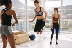 Femelle faisant la séance d'entraînement de corde à sauter au gymnase Photographie stock libre de droits