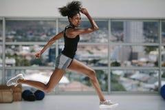 Femelle faisant la séance d'entraînement physique intense dans le studio de forme physique images stock
