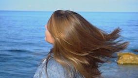 Femelle heureuse de mouvement lent la jeune développe des cheveux et pose sur l'appareil-photo, se tenant sur le bord de la mer s banque de vidéos