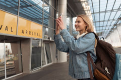 Femelle heureuse faisant des photos par le téléphone portable près de l'aéroport Photo stock