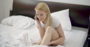 Femelle inquiétée à son lit parlant par le téléphone banque de vidéos