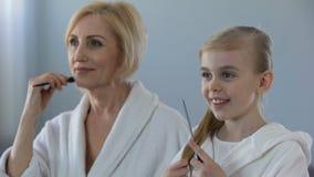 Femelle mûre et petite-fille peignant des cheveux et souriant devant le miroir clips vidéos