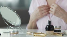 Femelle mûre touchant son cou et visage, utilisant des cosmétiques d'anti-âge, plan rapproché clips vidéos