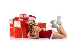 Femelle magnifique dans l'équipement de Noël se trouvant près de la pile de prese photographie stock