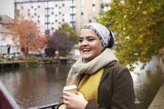 Femelle musulmane britannique avec du café à emporter par la rivière dans la ville Images stock