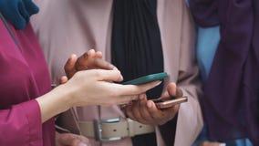 Femelle musulmane de jeunes affaires de couples utilisant le contact futé de téléphone avec l'associé banque de vidéos