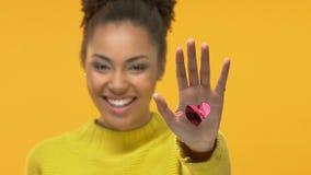 Femelle noire gaie montrant le coeur rouge à disposition sur le fond jaune, vacances banque de vidéos