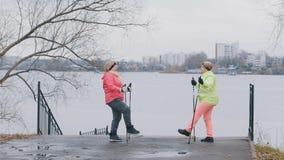 Femelle pluse âgé en parc d'automne faisant l'échauffement avant la marche nordique Photo libre de droits