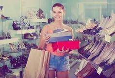 Femelle positive d'adolescent tenant des boîtes dans la boutique de chaussures Photographie stock libre de droits