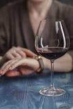 Femelle prenant le déjeuner avec le vin rouge dans un café ou un restaurant Image stock