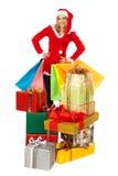 Femelle restant derrière la pile des cadeaux de Noël Images stock