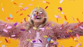 Femelle retirée heureuse jetant le mouvement lent de confettis colorés, ayant la partie d'amusement banque de vidéos