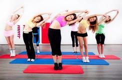 Femelle s'étirant dans une classe d'exercice d'aérobic Image libre de droits