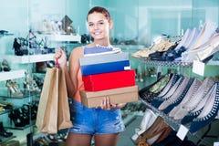 Femelle satisfaisante d'adolescent tenant des boîtes dans la boutique de chaussures Image libre de droits