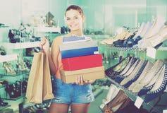 Femelle satisfaisante d'adolescent tenant des boîtes dans la boutique de chaussures Photos libres de droits