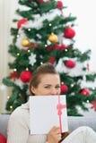 Femelle se cachant derrière la carte postale de Noël Photos stock