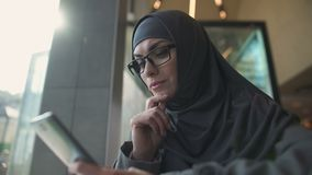 Femelle songeuse dans l'habillement musulman traditionnel causant au téléphone, opérations bancaires en ligne banque de vidéos