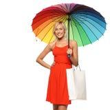 Femelle sous des sacs à provisions de fixation de parapluie Photos stock