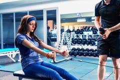 Femelle sportive faisant l'exercice physique avec son entraîneur Photos libres de droits