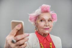 Femelle supérieure avec les cheveux roses prenant la photo sur le smartphone Photographie stock libre de droits