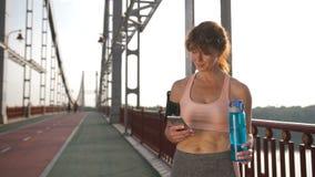 Femelle supérieure employant le sport APP au téléphone portable banque de vidéos