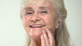 Femelle supérieure heureuse touchant la peau lisse de visage, hydratant l'effet de crème, soin banque de vidéos
