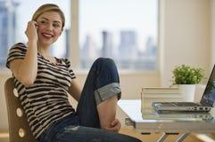 Femelle sur le bureau de téléphone portable à la maison Photo libre de droits