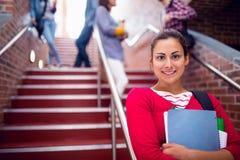 Femelle tenant des livres avec des étudiants sur des escaliers dans l'université Photographie stock libre de droits