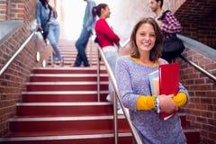 Femelle tenant des livres avec des étudiants sur des escaliers dans l'université Image stock
